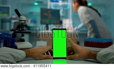 Pov Shot Of Chemist Using Smartphone With Green Screen In Biological Laboratory. Medical Worker Wear
