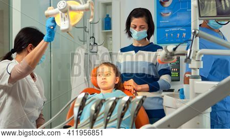 Orthodontist Lighting The Lamp Until Examining Kid And Patient Opening Mouth. Stomatologist Speaking