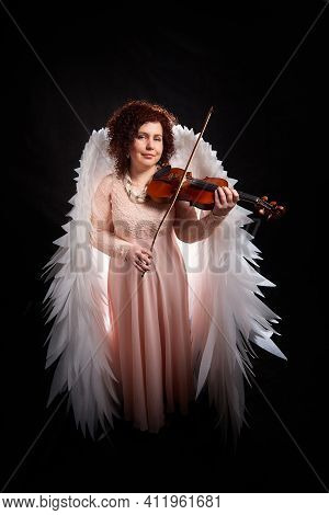 A Brunette Girl In An Elegant Dress, With Violin And White Angel Wings On A Black Background. Model,