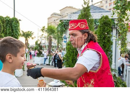 Moscow, Russia, September 01, 2019: A Man In Turkish National Costume Offers Ice Cream To A Boy