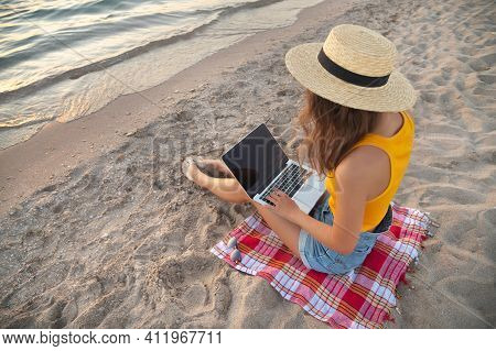 Young Caucasian Woman In Shorts And A Hat On The Beach Sitting On The Sand Browses Social Networks O