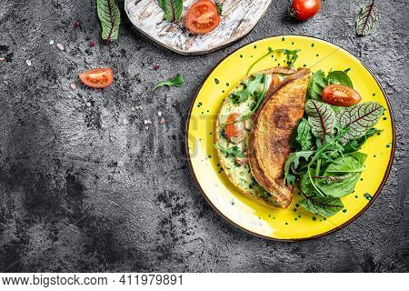 Frittata Made Of Eggs, Cheese And Spinach Salad. Frittata - Italian Omelet On A Yellow Plate On A Gr