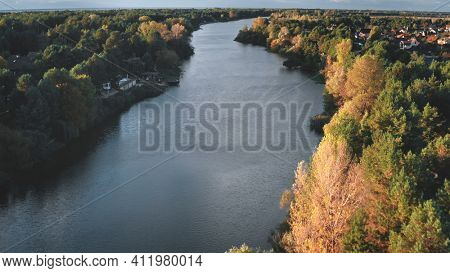 Cityscape at river shore aerial. Autumn nobody nature landscape. Colorful leafy trees forest at sun day. Cottages at city streets. Urban buildings at downtown suburbs. Green grass valley stream shore