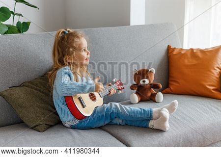 Cute Curly Girl Playing Ukulele And Singing For Teddy Bear At Home. 3 Years Old Kid Learning Guitar.