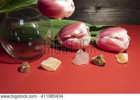 There Is A Glass Vase On The Table, Three Pink Tulips And Semi-precious Stones - Halite, Red Gypsum,
