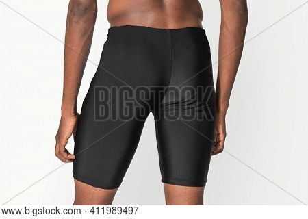 Man in black compression shorts for swimwear fashion shoot rear view