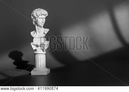 White Marble Head Of Young Man, Head Of Famous Statue. Gypsum Copy Of Ancient Statue Head On Purple