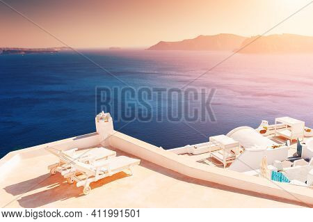 Beautiful Sunset At Santorini Island, Greece. Two Chaise Lounges On The Terrace With Sea View. Trave