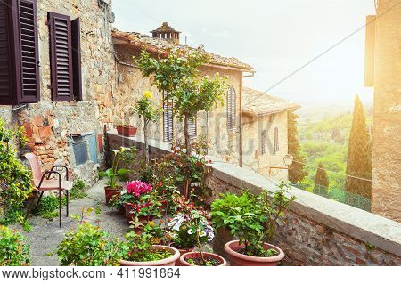 Beautiful Terrace With Flowers. Old Architecture In San Gimignano, Tuscany, Italy.