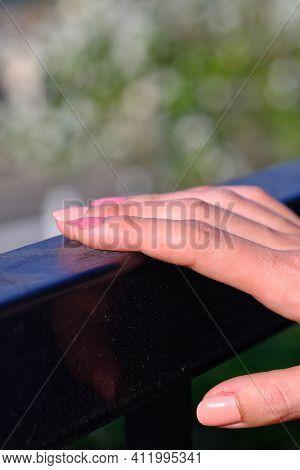 Closeup Of A Woman's Pink Fingernails Outdoors