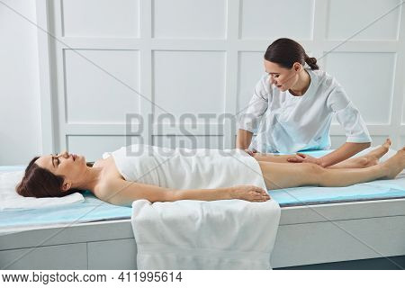 Charming Masseuse Massaging Woman Leg In Spa Salon