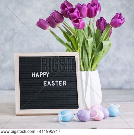 Spring Concept. Bouquet Of Purple Tulips Flowers And Letter Board With The Words Happy Easter. Happy