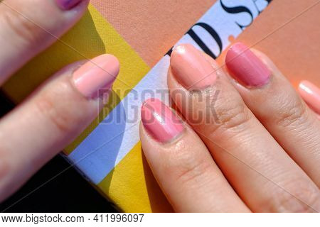 Close Up Of Beautiful Pink Fingernails Of A Young Woman And A Book