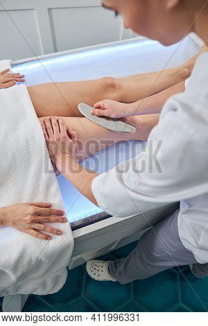 Masseuse Massaging Woman Leg With Medical Massager