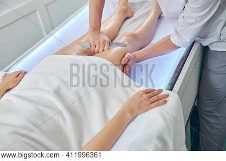 Masseuse Performing Therapeutic Massage With Metal Tool