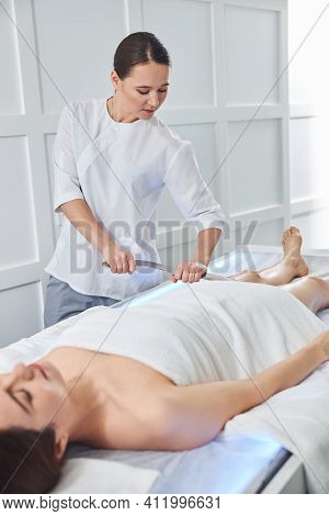 Charming Masseuse Doing Therapeutics Massage With Metal Tool