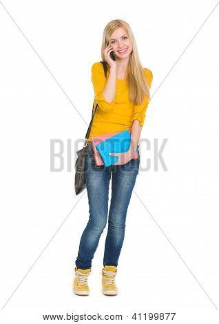 Full Length Portrait Of Happy Student Girl Speaking Mobile