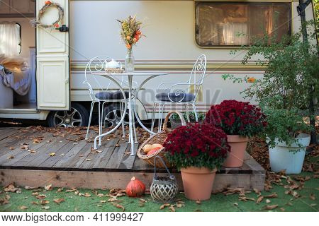 Interior Cozy Patio With Chrysanthemums In Pots. Table And Chairs With Tea Set  Placed Outside Cozy