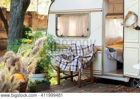 Interior Cozy Yard Campsite With Green Plants Potted. Wooden Armchair With Plaid Near Outside Retro