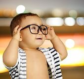 Portrait Of Baby Boy Wearing Eyeglasses against a city by night poster