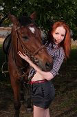 beautiful girl in a shirt and a horse near the tree poster
