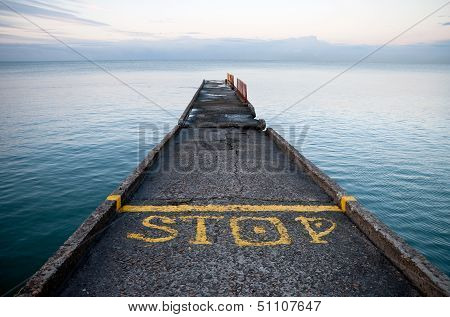 Pier perspective with yellow stop-line and Stop label on Black Sea coast. Russia Sochi Adler poster