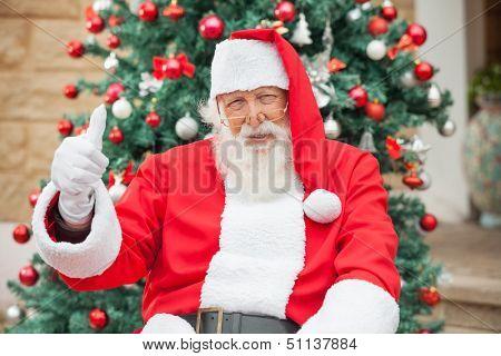Portrait of happy Santa Claus gesturing thumbsup against Christmas tree