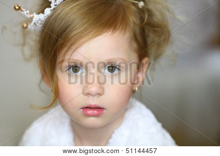 Facial portrait of a little girl with a crown on his head
