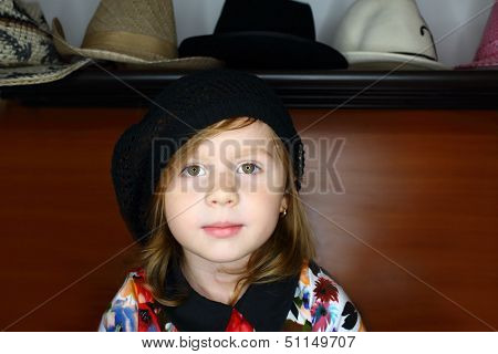 A little girl in a black knitted beret