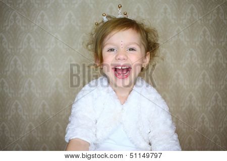 Portrait of a smiling little girl with a crown and rhinestones on his head