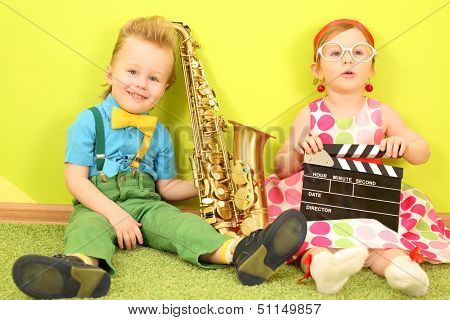 Little boy and girl sitting at a bright green wall with a trumpet and a clapstick