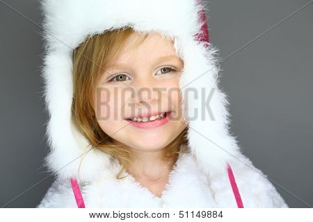 Portrait of a little girl in winter hat with white fur on a grey background