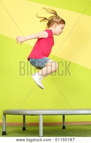 Little girl with pigtails jumping on a trampoline in the room with bright walls and floors