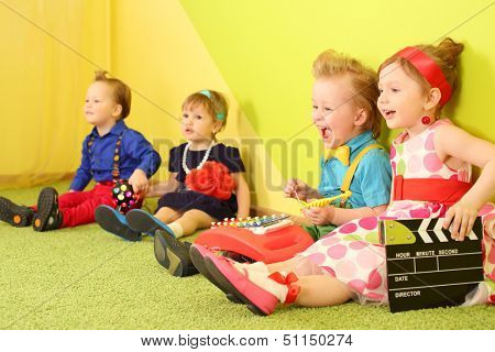 Four mods children sit at the bright wall with a metallophone and clapstick
