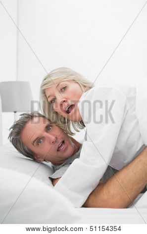 Embarrassed couple caught in the act at home in bed