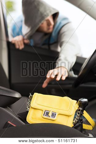 transportation, crime and ownership concept - thief stealing bag from the car poster