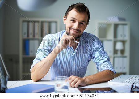Smart businessman looking at camera with smile in office