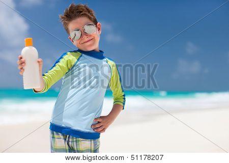 Cute little boy at tropical beach holding a bottle of sunblock