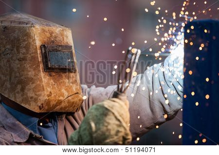 Heavy industry welder worker in protective mask hand holding arc welding torch working on metal construction
