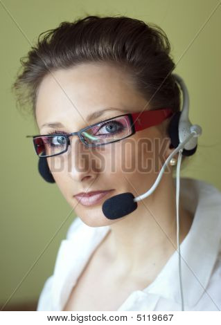 Women In Red Glasses With Headset Phone At A Call Center