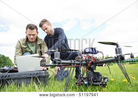 Young male engineers using laptop by UAV octocopter in park