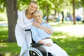 Pretty nurse and senior patient in a wheelchair looking at camera outside poster