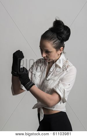 Fashion portrait of beautiful caucasian female model wearing white shirt and wearing fingerless gloves