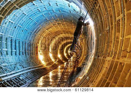Tuneller welder working with electrode at arc welding in underground subway metro construction site