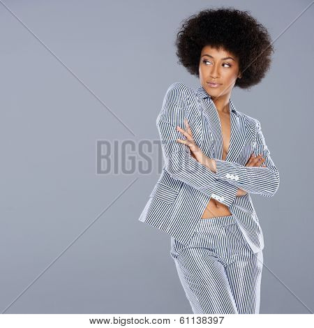 Beautiful glamorous Afro-American woman in a stylish tailored striped slack suit standing looking at her right