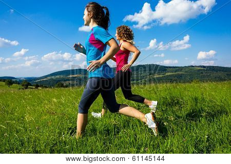 Healthy lifestyle - two women running, jumping outdoor