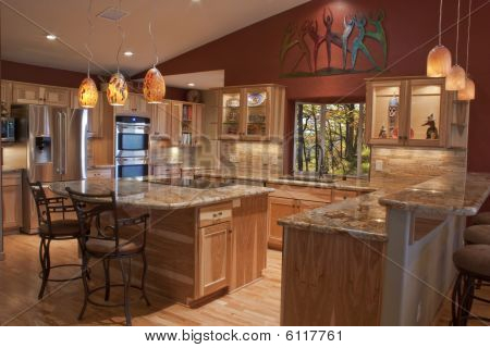 A luxury remodeled kitchen with granite counter tops and stainless steel appliances poster