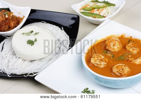 Top View of Goan Prawn Curry which is made from fresh prawns are cooked in spicy masala and served with Goan style idly poster