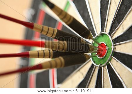 Five darts hitting bullseye on dartboard