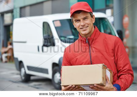 Smiling male postal delivery courier man outdoors  in front of cargo van delivering package